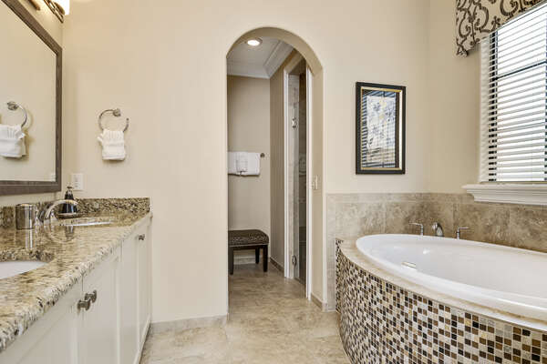 En-suite bathroom has dual sink, garden tub, and glass walk-in shower