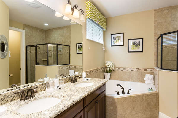 En-suite master bathroom has a walk in shower, garden tub, and dual vanity