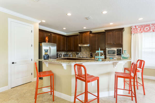 Fully equipped kitchen with stainless steel appliances and breakfast bar with seating for 4