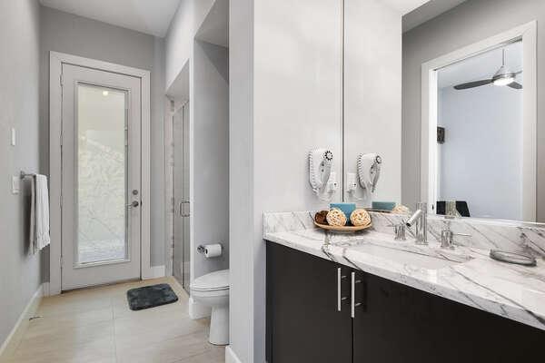 The en-suite bathroom features a glass door walk-in shower, marble vanity, and access door from the hallway