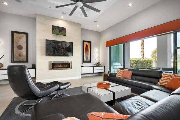 The living area features a 65-inch TV and 32-inch TV