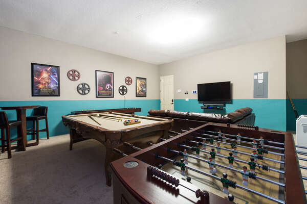 The games room features a pool table, foosball table, and comfortable seating