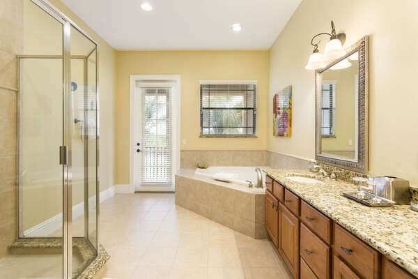 The master bathroom is spacious and offers a glass walk-in shower and large soaking tub
