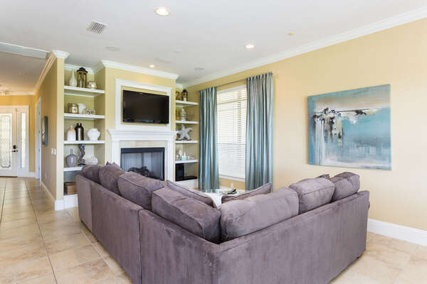 The living room featurs a large flatscreen TV and fireplace