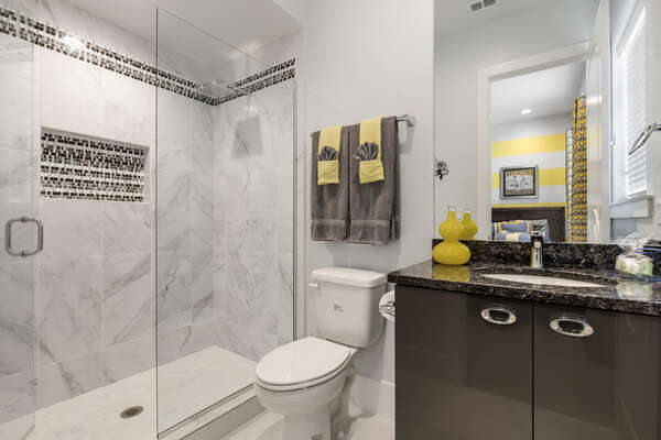 The ensuite bathroom perfectly matches the bedroom with pops of grey and yellow