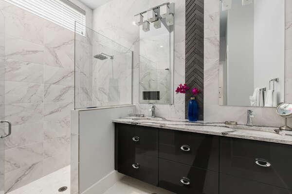 The ensuite bathroom has a large walk-in glass shower and double sinks