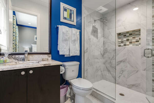 This bathroom is complete with a glass walk-in shower and granite countertops