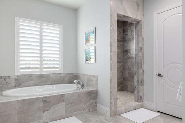 En-suite bathroom features a walk-in shower, dual vanity, and garden tub