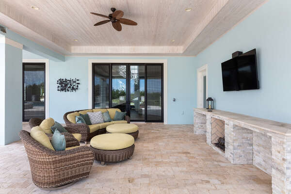 The covered lanai features a TV, and plenty of seating for all (Disclaimer: Fireplace(s) not allowed for guest use, homeowner use only.)