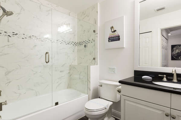 The large and spacious shared family bathroom has a combination shower and bathtub