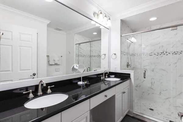 The ensuite master bathroom features a walk-in shower and his and hers sinks