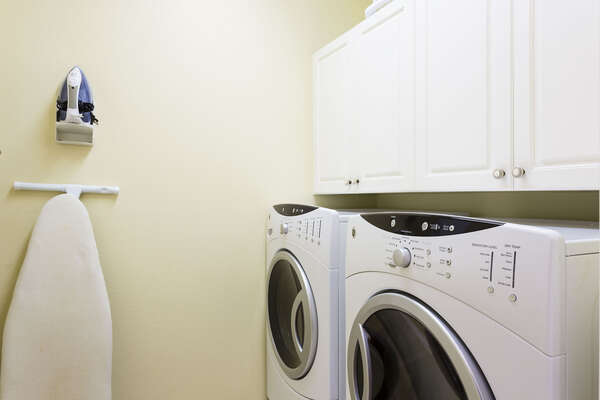 Laundry room with full-size washer and dryer, ironing board and iron