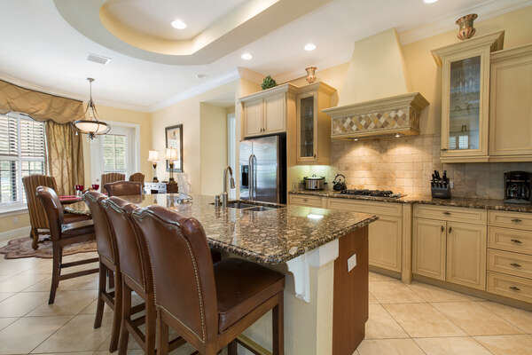 Fully equipped eat-in kitchen with stainless steel appliances, custom cabinetry & granite countertops
