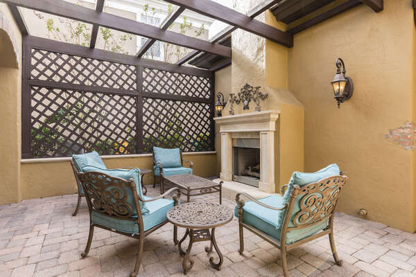 Private courtyard with lounge chairs, an outdoor fireplace and a soothing water fountain