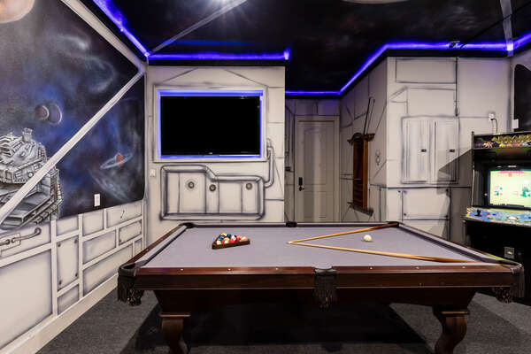 The games room has a pool table and classic arcade machine to play all day long