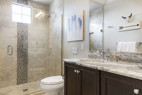 En-suite bathroom with glass walk-in shower and dual vanity