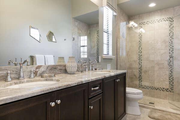 En-suite bathroom with granite dual vanity and glass walk-in shower