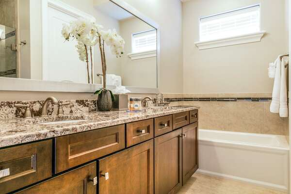En-suite bathrrom with dual vanity, walk-in shower, and tub