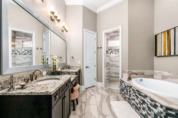 En-suite bathroom with dual vanity, walk-in shower, and garden tub for relaxation