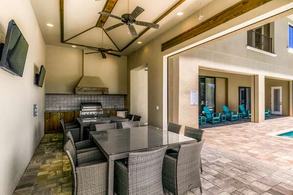 Dine al fresco in the summer kitchen with built-in BBQ, outside dining table, and TVs