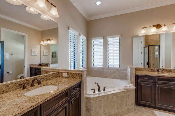 The master bathroom has double sinks and a relaxing bath tub