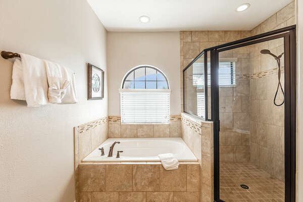 A glass walk-in shower and garden tub