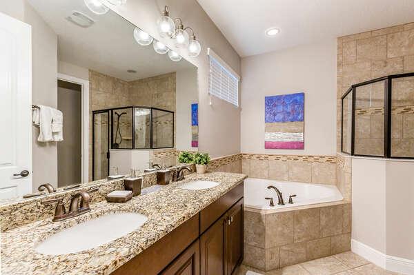 The master suite en-suite bathroom with dual vanity, garden tub, and walk-in shower