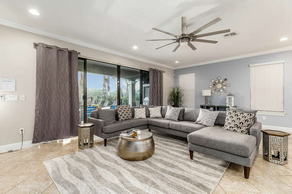 The living area has a comfortable seating for all with a beautiful pool view