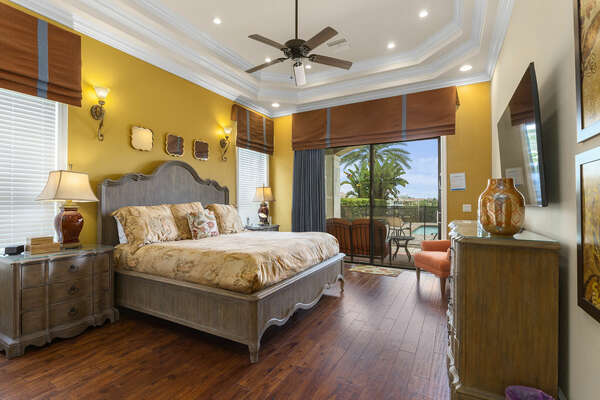 Decorative downstairs master suite bedroom 2 featuring a beautiful tray ceiling