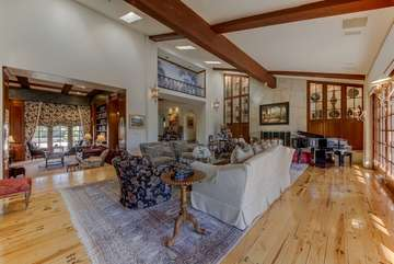 The family room with baby grand piano leads into the library