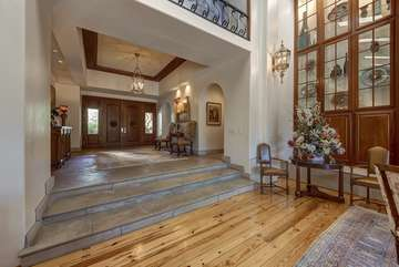 The stunning grand foyer has tall ceilings inside as you first walk into this huge 1 story estate with an immediate view of the Santa Rosa mountains through the large widows in front