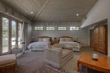 Casita bedroom. Bedroom 5. Two Queens, en suite bathroom, patio access, exercise bike, TV and sofa