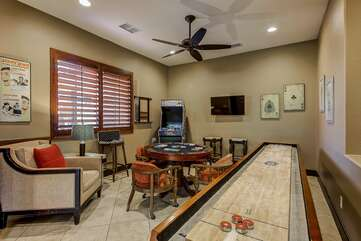 Man cave type game room with shuffleboard, stand up retro 80's video game machine, TV, poker table
