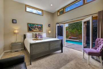The Master Bedroom Suite features a King-size bed, Queen sofa sleeper,  Smart TV, and private double french doors that lead to the pool and spa.