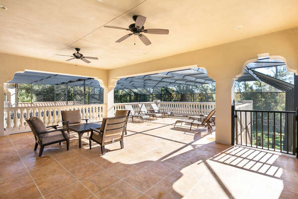 The second floor patio features comfortable seating and an outdoor TV