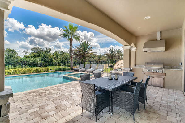 The home features a summer kitchen and outdoor dining table for 6 to enjoy a meal al fresco