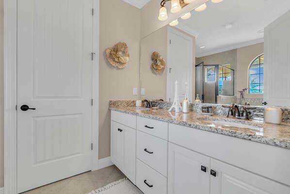 The lavish ensuite master bathroom continues the Parisian theme