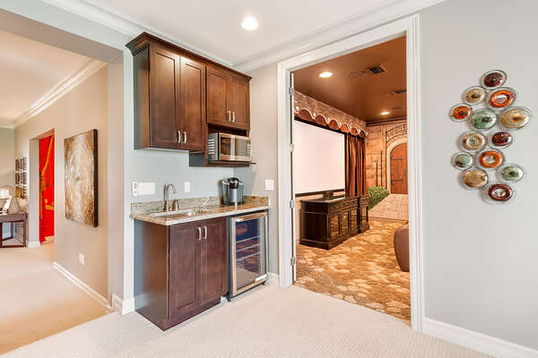 The wet bar is located in the game room next to the theater room