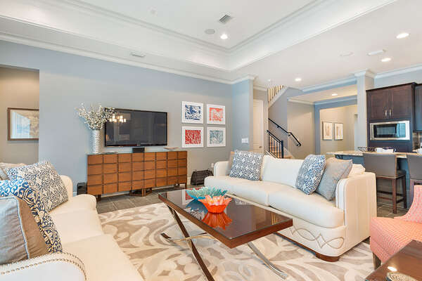 The living area features a 60-inch TV and ample seating