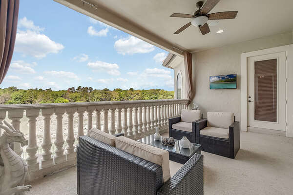 Upstairs balcony with comfortable seating and an outdoor TV