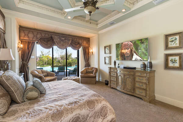 The master suite features a king size bed, 65-inch 7 Series SMART TV, access to pool area, and en-suite bathroom