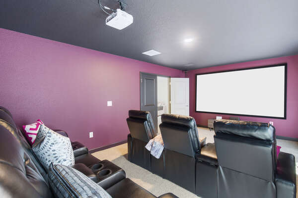 The second floor theater room features a 120-inch projection screen and plush armchair seating