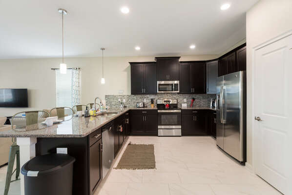 The kitchen features stainless steel appliances and beautiful granite countertops