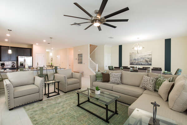 The open living area is beautifully decorated with neutral colors and plush comfortable furniture