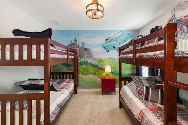 The bedroom has custom painted artwork on the walls