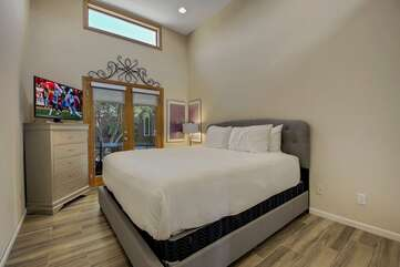 Bedroom 5 has a King-sized bed, Smart TV, reach-in closet and exterior doors to the ping pong patio.