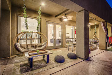 Located just outside the main living space and kitchen is a love swing for two and the outdoor dinning space.