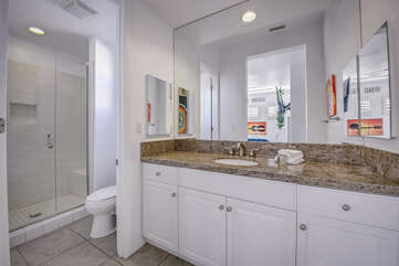 The private en Suite bathroom features a tile shower and granite countertop.