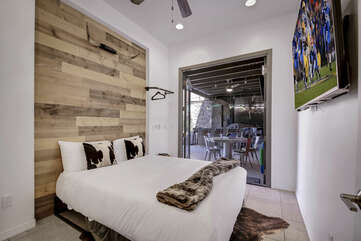 Bedroom 6 has a Queen-sized bed, 65-inch Smart TV and French doors that open up to the outdoor game area.