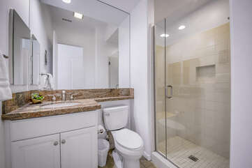 Hallway bathroom features a tile shower and granite countertop.